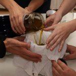 Vier Hände schütten Öl durch ein Tuch in ein Glas